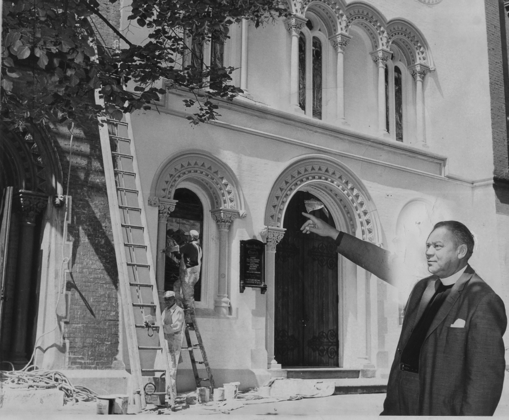 Recently appointed Rector Rev. Nelson F. Parke proudly points to the newly painted St. Paul's, 9 July 1960.  Times Union staff photo taken by Wilder. Used by permission of the Times Union.