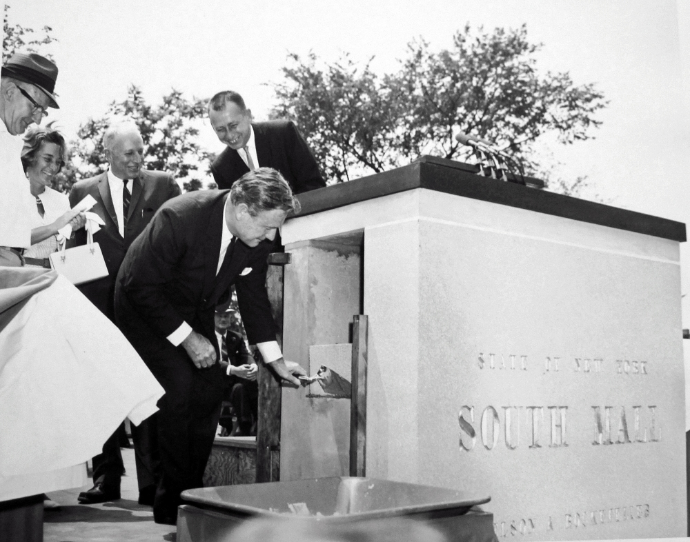 Mason for a day, Gov. Rockefeller helps seal the document box in the South Mall cornerstone. Frank Snyder, Happy Rockefeller, Mayor Corning, Lt. Gov Wilson look on. NYS Archives.