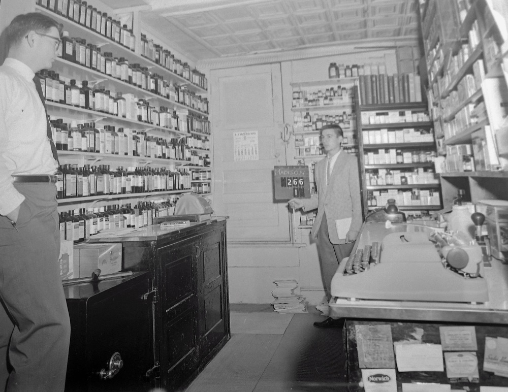 In the prescription room. Ken Jr, also a pharmacist, stands facing a state agent. NYS Archives.