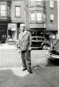 Dressed for work, Lazarus stands on the sidewalk in front of the family's store, ca. 1950. Courtesy of Angelo Kontis.