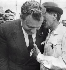 An unidentified man whispers in the governor's ear.